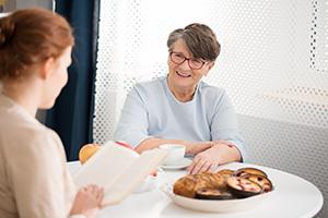 24-h-Pflegerin & Seniorin trinken zusammen Kaffee
