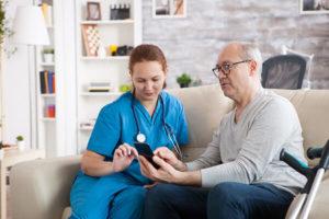 Pflegedienst-Mitarbeiterin besucht älteren Herren