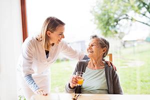24-Stunden-Betreuerin spricht mit älterer Dame