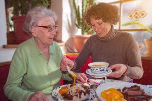 Senioren und Pflegekraft leben gemeinsam
