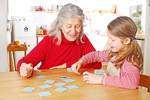 Seniorin und Enkelin spielen Memory