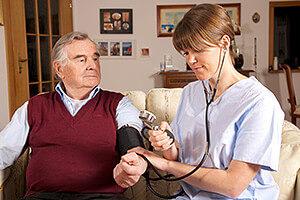 Pflegedienst misst Blutdruck bei Senior