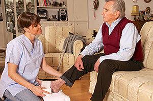 Pflegedienst verbindet Fuß eines älteren Herrn