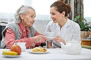 Betreuungskraft und Seniorin beim Essen