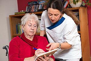 Betreuerin hilft Seniorin bei der Antragstellung