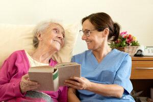 Bettlägerige Seniorin und Pflegekraft lesen Buch