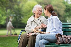 Betreuerin mit Seniorin im Park