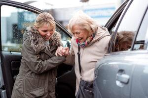 Pflegekraft hilft Seniorin aus Auto