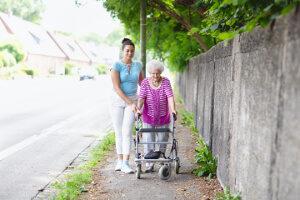 Pflegekraft und Seniorin mit Rollator unterwegs