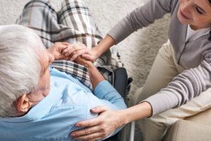 Pflegekraft sitzt zu Hause neben Pflegebedürftigem