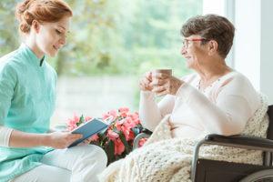 Betreuerin liest Seniorin zu Hause vor