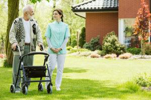 Osteuropäische Betreuerin und Patient spazieren im Garten