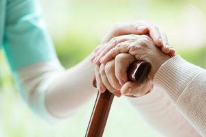 Hände von polnischer Pflegerin und Patientin