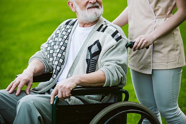 Ganztagsbetreuerin schiebt Herren in Rollstuhl