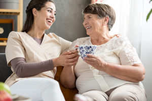Betreuungskraft aus Polen und Seniorin trinken Tee