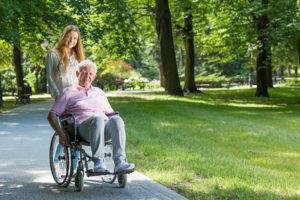 24-Stunden-Pflegekraft schiebt Patient durch den Park
