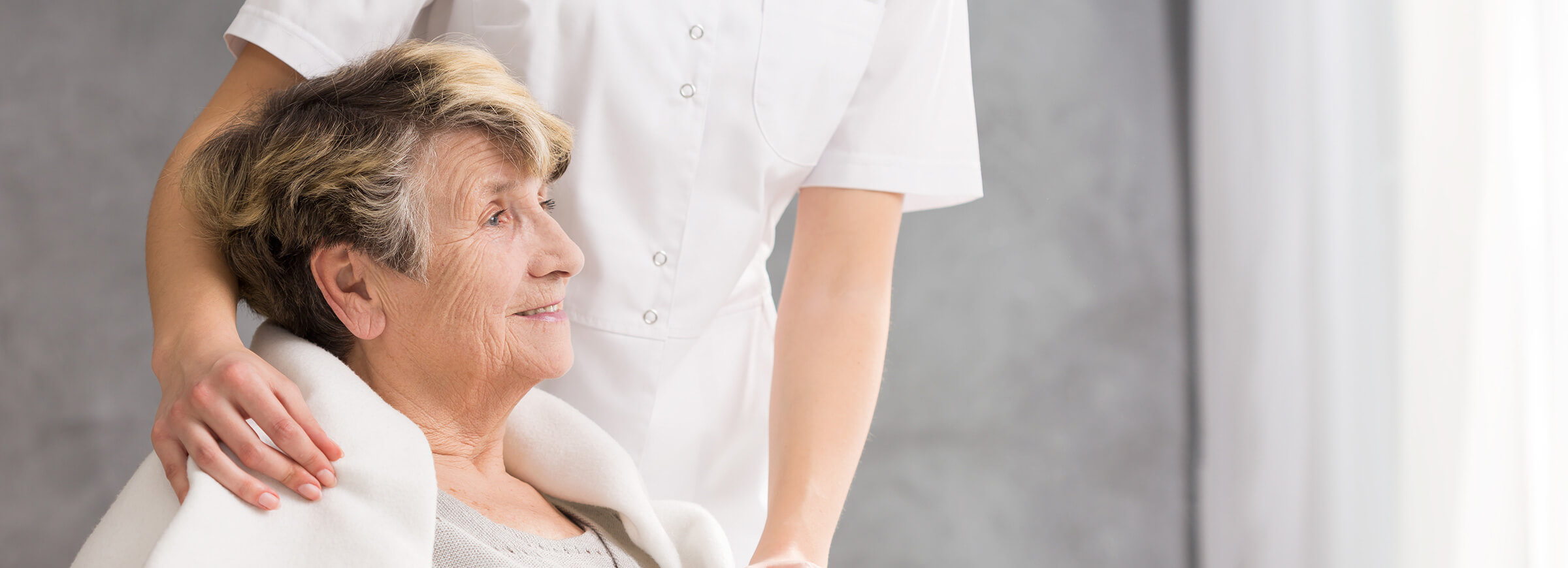 Demenzbetreuerin steht hinter älterer Dame
