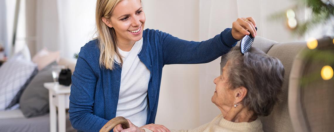 24-Stunden-Pflegekraft kämmt ältere Frau