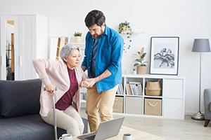 24-Stunden-Pfleger hilft ältere Dame beim Aufstehen