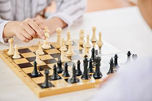 24-h-Betreuerin beim Schachspiel mit älterem Herrn