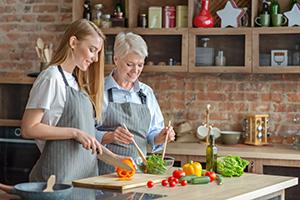 Ältere Dame und Betreuerin machen einen Salat