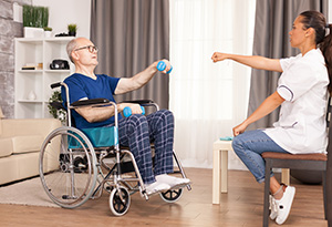 Pflegerin macht Übungen mit Mann im Rollstuhl