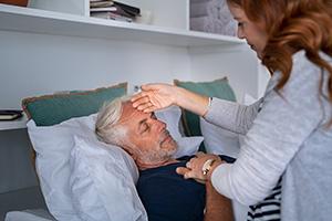 Pflegerin prüft Temperatur eines älteren Mannes