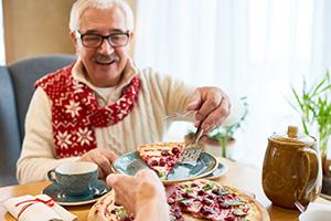 Senior und Pflegekraft essen gemeinsam Kuchen