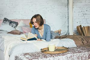 24-Stunden-Betreuerin liest ein Buch in ihrem Zimmer