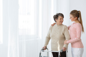 Betreuungskraft holt Seniorin zum Spaziergang ab