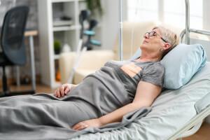 Frau liegt nach einem Schlaganfall zu Hause im Pflegebett