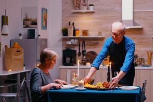 Älterer Herr serviert selbstgekochtes Essen in seiner betreuten Wohneinrichtung