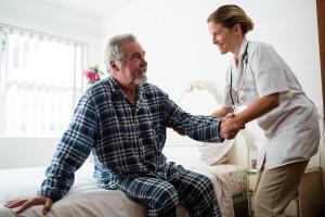 Ärztin besucht Senior in seiner Wohnung der betreuten Wohneinrichtung