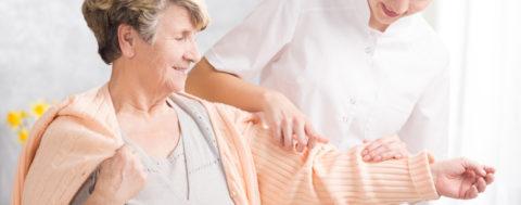 Betreuerin hilft einer älteren Frau nach Schlaganfall beim Anziehen