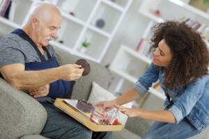 Präsenzbetreuerin serviert einem Senioren-WG-Bewohner sein Essen