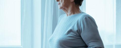 Eingeschränkt sehfähige Frau am Fenster ihres Zuhauses