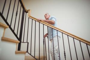 ALT: Parkinson-Patient mit Gehstock beim Treppensteigen