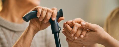 24-Stunden-Pflegekraft hält die Hand einer Seniorin mit Stock