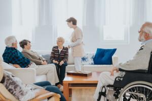 Ärztin hilft Pflegeheimbewohner aus dem Bett