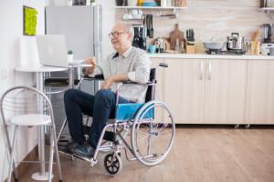Älterer Herr im Rollstuhl im barrierefreien Zuhause
