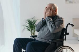 Trauriger Mann sitzt nach Schlaganfall im Rollstuhl