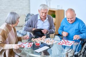 Seniorengruppe spielt im Aufenthaltsraum einer betreuten Wohneinrichtung