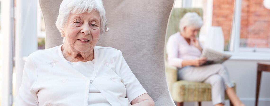 Ältere Damen sitzt im Aufenhaltsbereich einer Pflegeeinrichtung