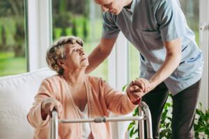 Betreuungskraft hilft Seniorin bei der Nutzung der Gehhilfe